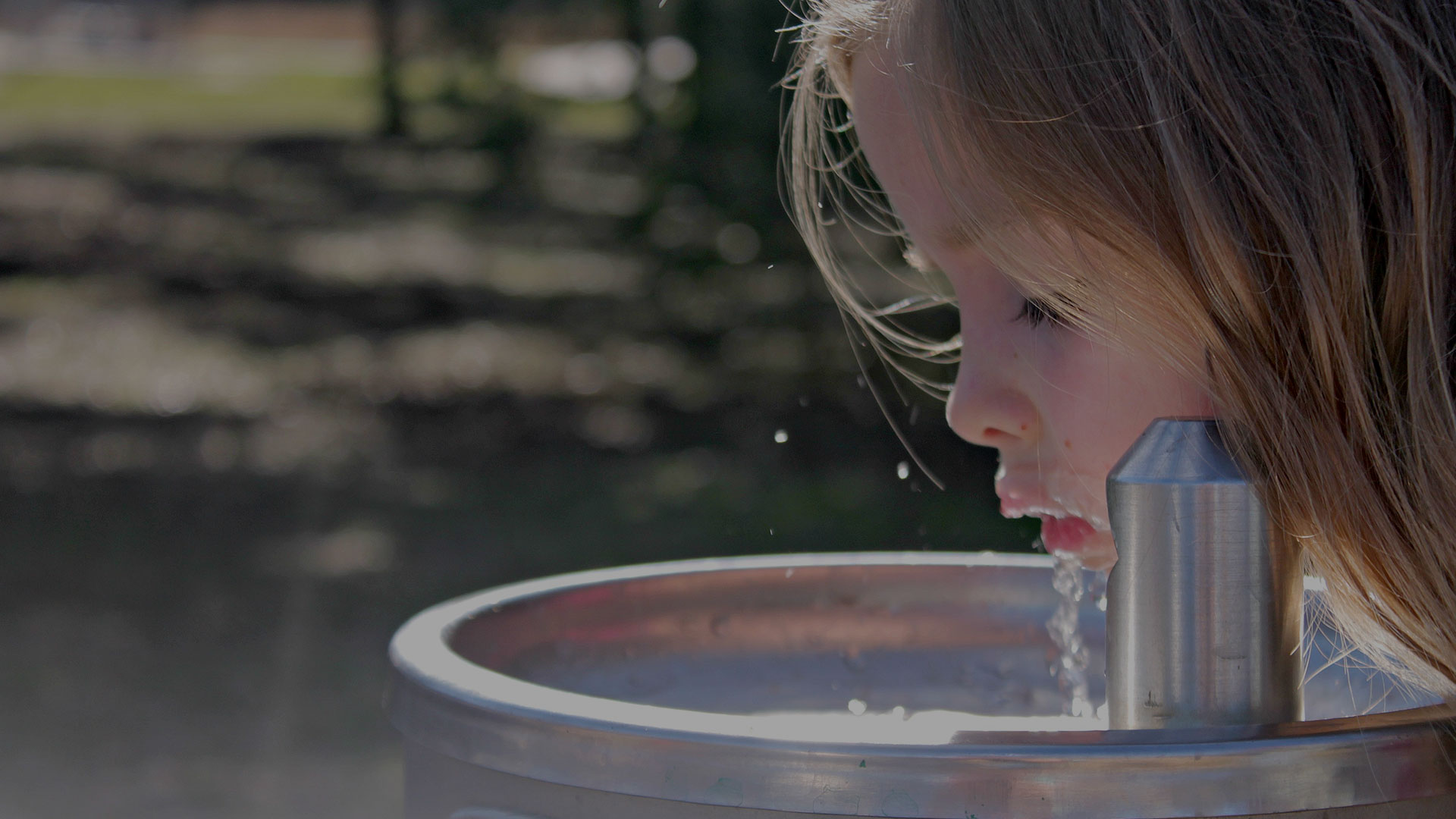 Girl drinking water from Community fountain
